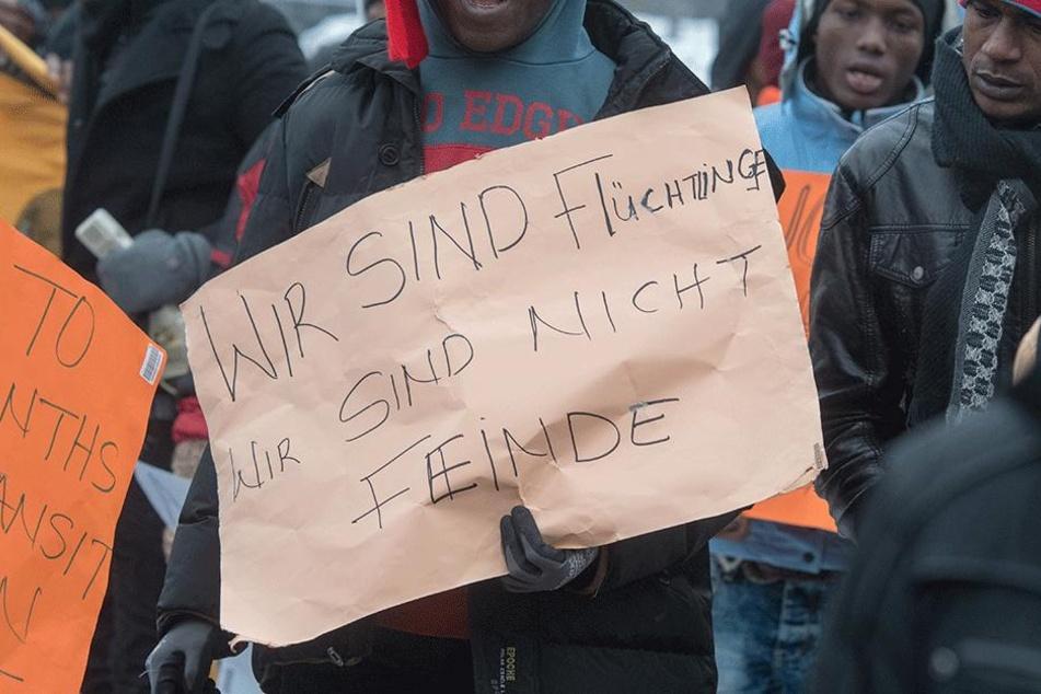 """""""Wir sind Flüchtlinge. Wir sind nicht Feinde"""", steht auf einem Transparent."""