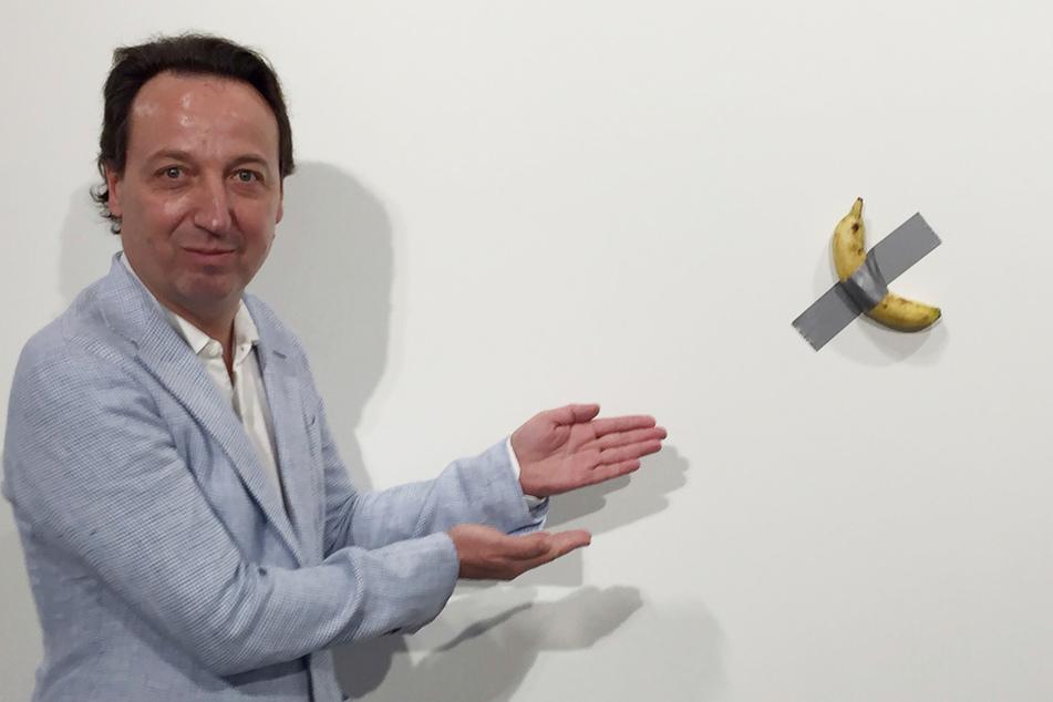 """Dezember 2019: Galerist Emmanuel Perrotin zeigt auf das Kunstwerk """"Comedian"""" von Maurizio Cattelan auf der """"Art Basel""""-Ausstellung in Miami. Diese für 120.000 Dollar als Installation verkaufte Banane ist später auf der Art Basel vor den Augen perplexer Besucher von einem Aktionskünstler verspeist worden."""