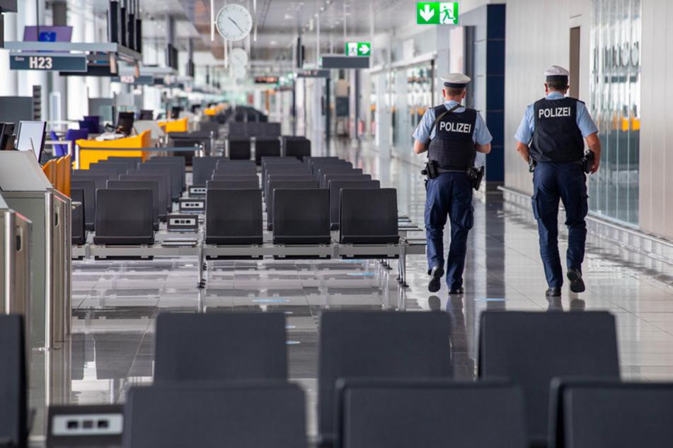 Zwei Polizisten mit Mund-Nasen-schutzmaske laufen durch den noch menschenleeren Flughafen-Terminal 2 Streife.