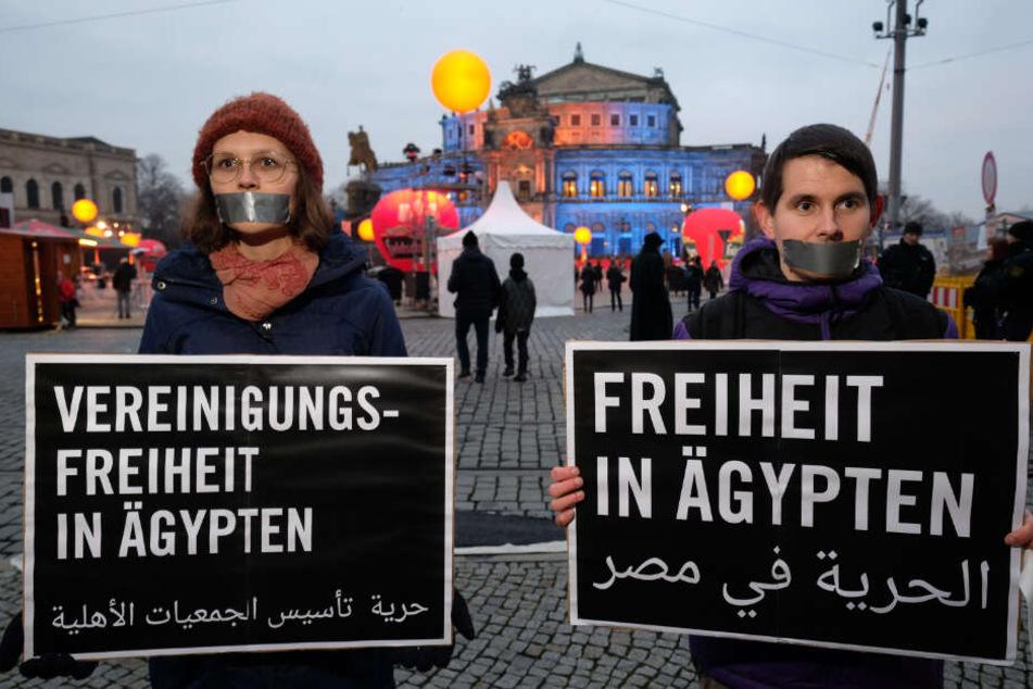 Aktivisten von Amnesty International stehen mit Transparenten während einer Demonstration vor der Semperoper.