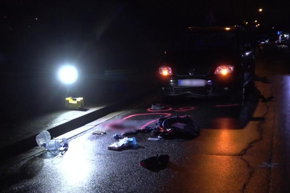 Frau liegt auf der Straße und wird von Auto überrollt