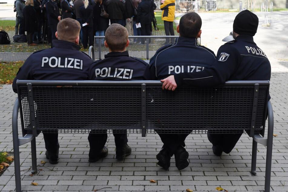 Polizeischüler sitzen vor der Polizeiakademie auf einer Parkbank. (Symbolfoto)