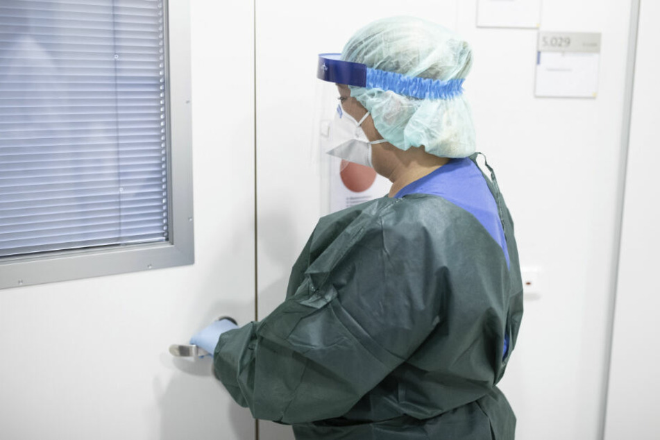 Canan Emcan, Stationsleiterin auf der Infektionsstation der Uniklinik Essen, steht in Schutzkleidung und mit einer Atemmaske in einer Schleuse vor einem Patientenzimmer.