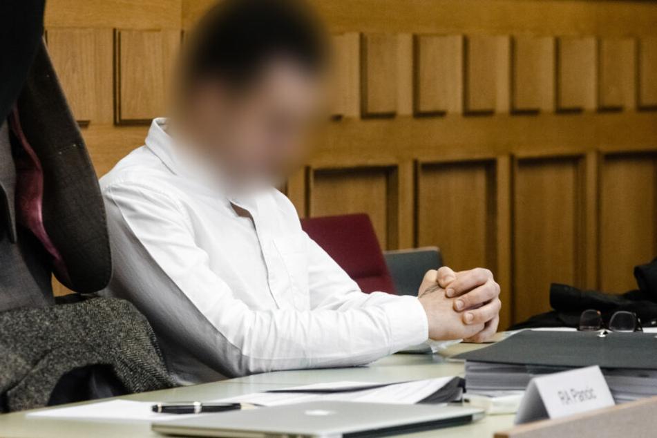Der 25-jährige Angeklagte sitzt in einem Verhandlungssaal des Amtsgerichts Ahrensburg.