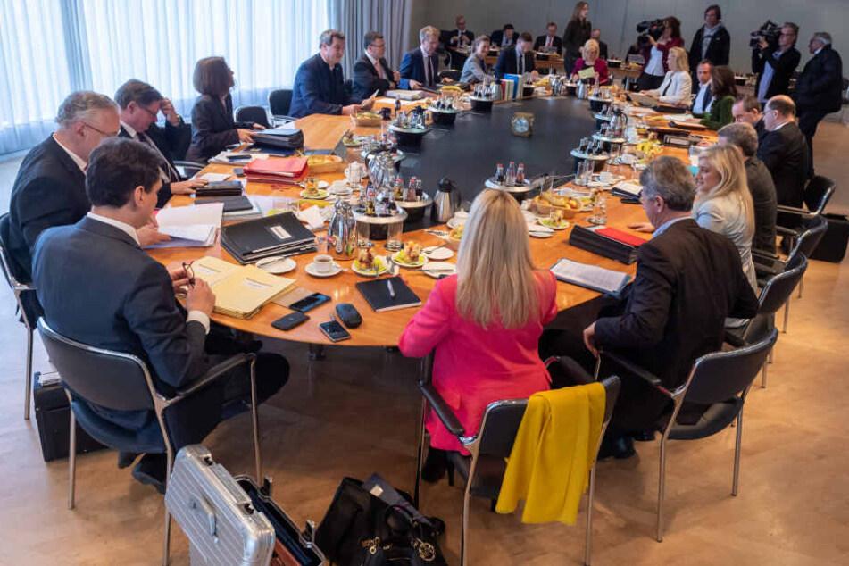 Die Mitglieder der bayerischen Staatsregierung sitzen zu Beginn der Kabinettssitzung am ovalen Tisch zusammen.