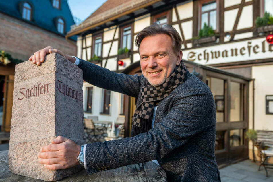 Zwei Bundesländer, ein Hotel: Hotelchef Andreas Barth (55) am Grenzstein von Thüringen und Sachsen.