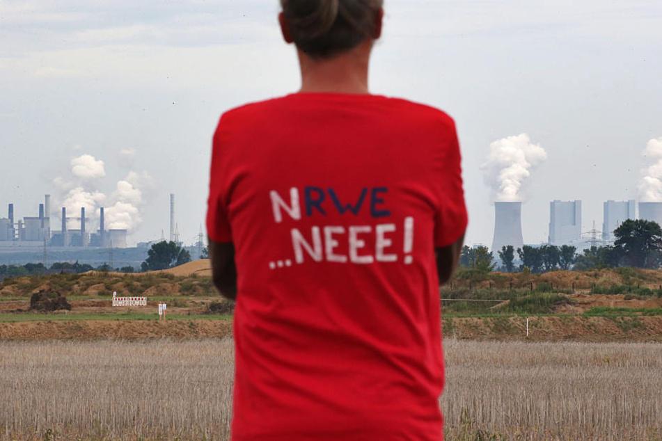 Ein Demonstrant am Randes des Tagebaus Hambach vor der Kulisse des RWE Braunkohlekraftwerks. (Symbolbild)