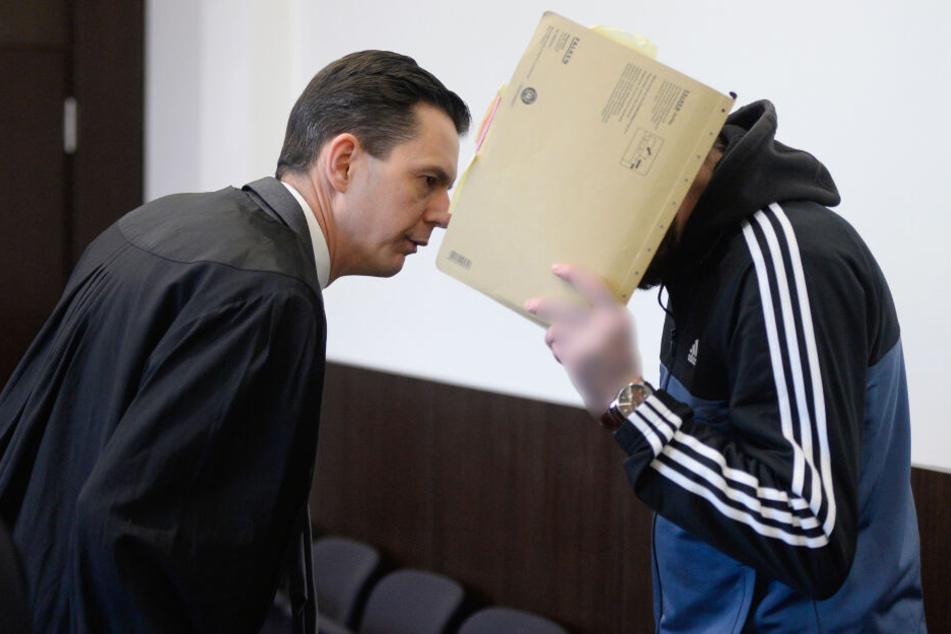 Der Angeklagte (r) spricht vor dem Prozessauftakt mit seinem Rechtsanwalt.