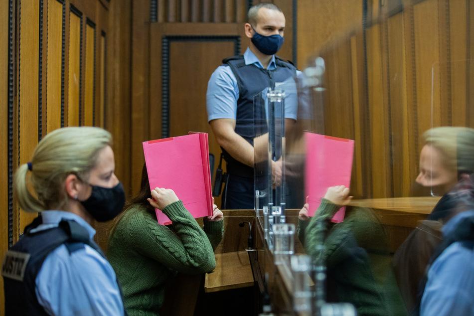 Die Angeklagte sitzt in einem Gerichtssaal des Landgerichts zwischen Justizvollzugsbeamten.