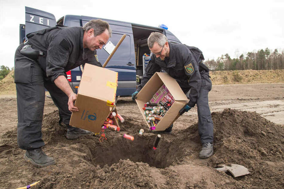Die Kriminalhauptkommissare kippen kistenweise beschlagnahmte Pyrotechnik in das Böller-Grab.