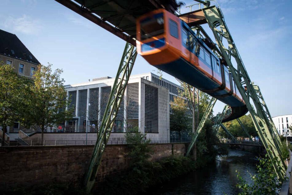 Eine Schwebebahn fährt am Justizzentrum in Wuppertal vorbei.