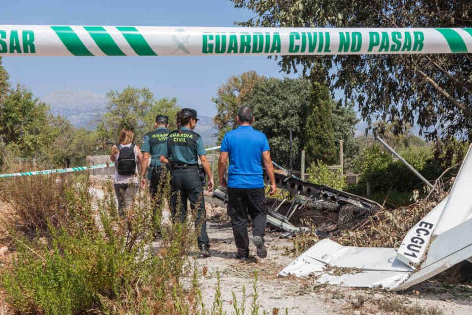 """Die Absturzstelle ist mit einem Absperrband der """"Guarda Civil"""" abgesperrt, Mitglieder der Polizeieinheit """"Guardia Civil"""" stehen mit zwei anderen Personen hinter einem Teil des Flugzeugwracks."""