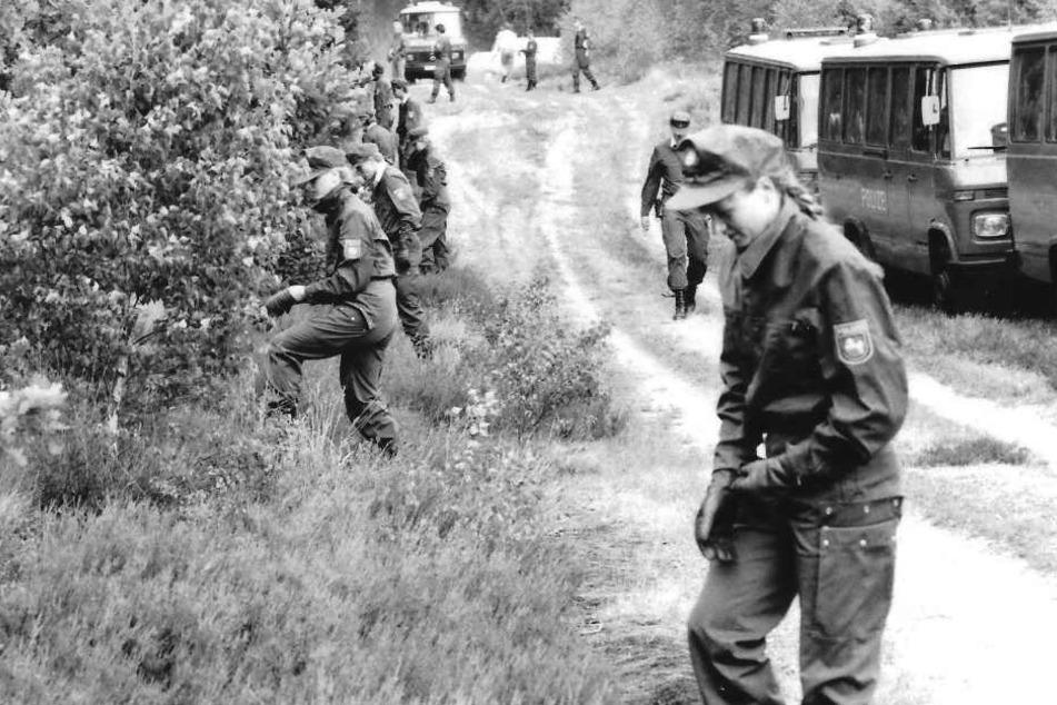 Polizisten durchsuchen den Wald in der Göhrde nach Spuren der Täter, die ein Hamburger Ehepaar getötet hatten.
