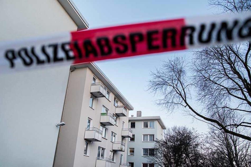 Ein Absperrband der Polizei hängt vor Mehrfamilienhäusern in Essen. Hier war in einer Wohnung die Frau getötet und eine weitere schwer verletzt worden.