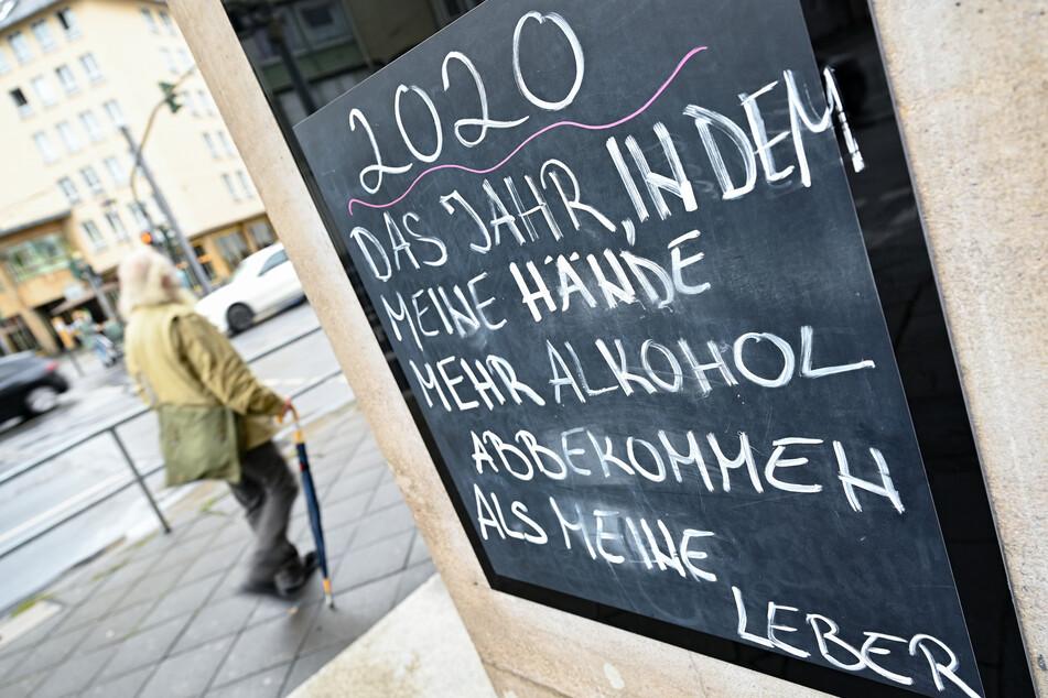 """Neben dem Eingang eines Lokals in der Frankfurter Innenstadt prangt eine Tafel mit der Aufschrift """"2020 - Das Jahr, in dem meine Hände mehr Alkohol abbekommen als meine Leber""""."""
