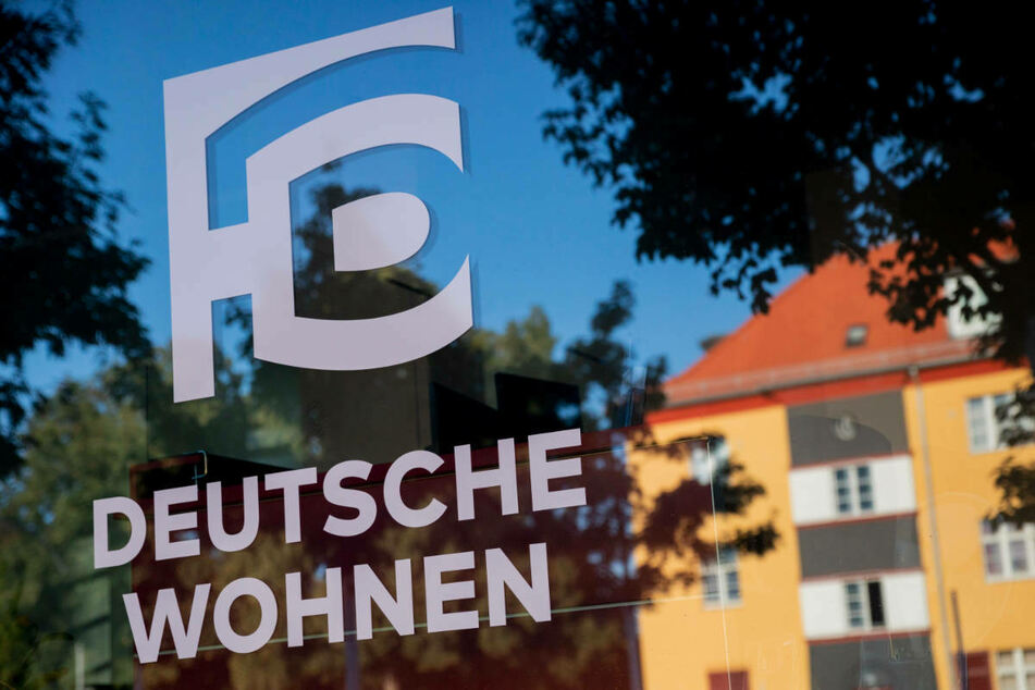 Das Logo von Deutsche Wohnen ist auf der Fensterscheibe eines Vermietungsteams in der Hufeisensiedlung in Berlin-Neukölln zu sehen. Deutschlands größter Wohnungskonzern Vonovia will den Berliner Marktführer unbedingt übernehmen.