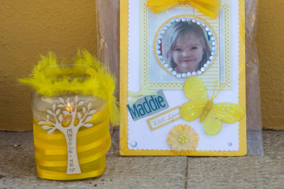 Eine Kerze und ein Porträtfoto von Madeleine McCann stehen in Praia da Luz (Portugal).