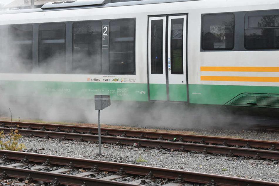 Riesiger Mann schmeißt Steine auf Zug und schlägt Scheiben ein