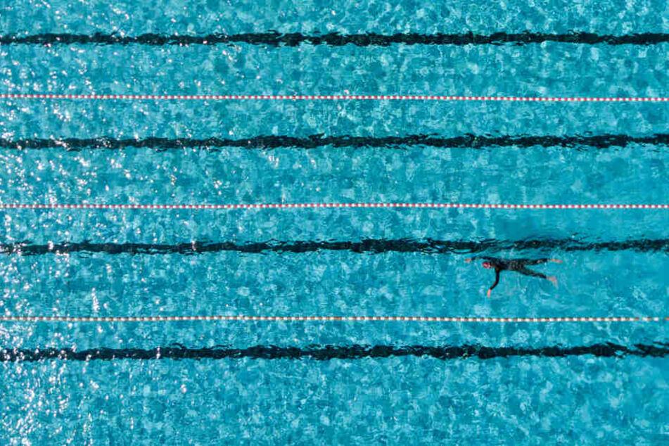 Ein Badegast schwimmt in einem Hamburger Freibad im 50-Meter-Becken.