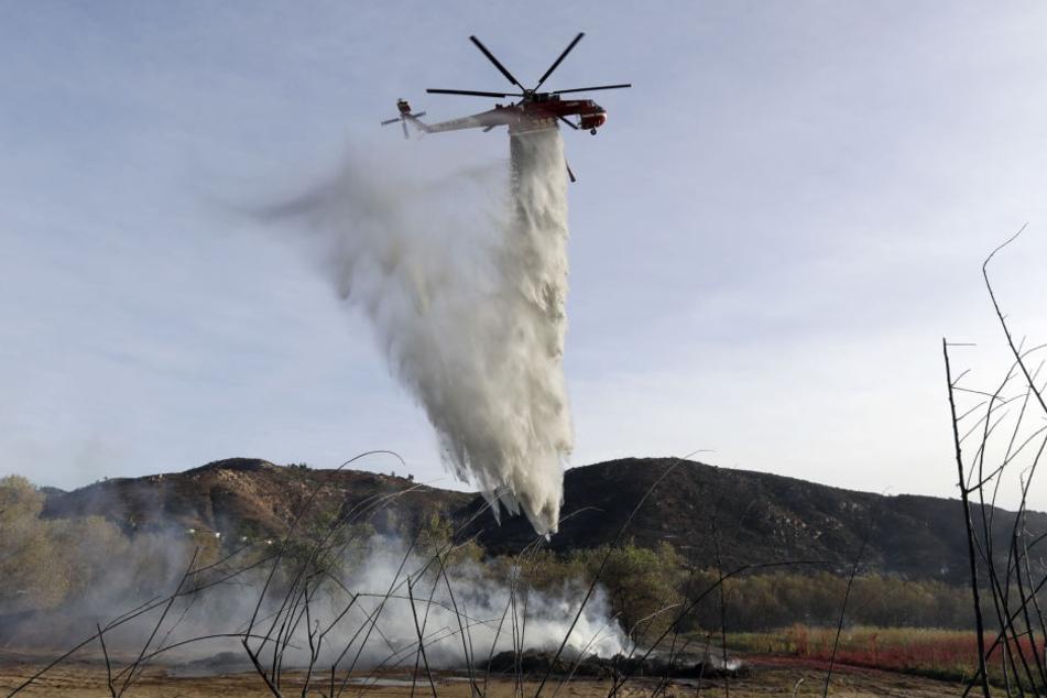 Ein Löschhubschrauber wirft in Fallbrook, Kalifornien, USA, seine Wasserladung über einem Schwelbrand von Holzschnitzeln und Mulch ab.