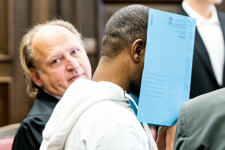 Der Angeklagte verbirgt sein Gesicht vor der Presse hinter einem Aktenordner (Archivbild). Neben ihm sitzt sein Anwalt Tim Burkert.