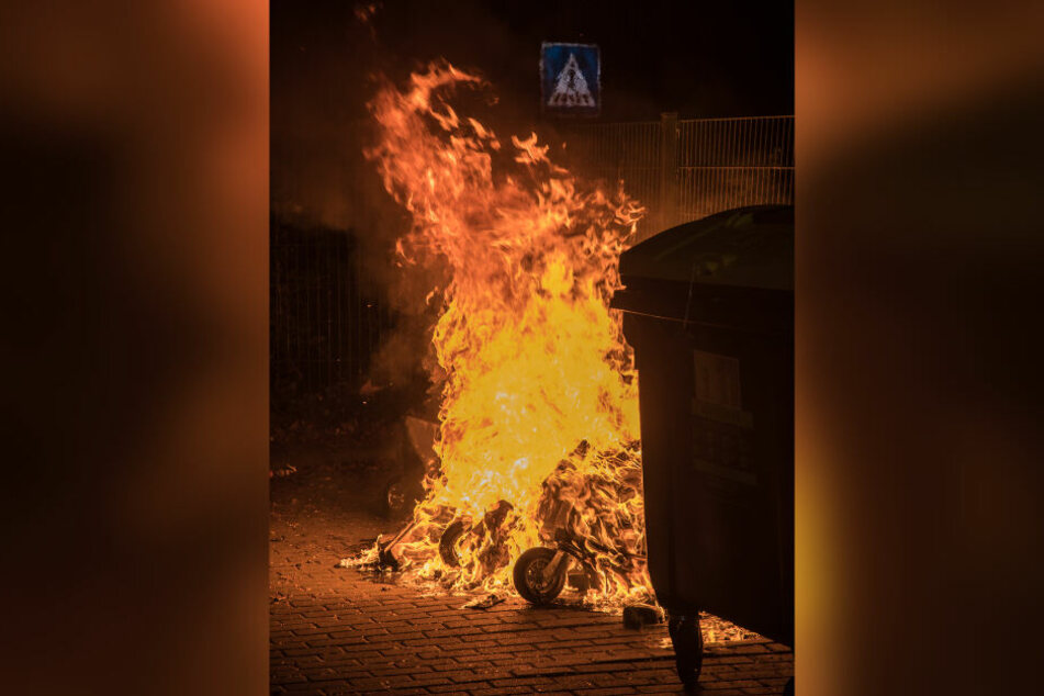 Flammen schlagen aus der bereits völlig in sich zusammen geschmolzenen Mülltonne.