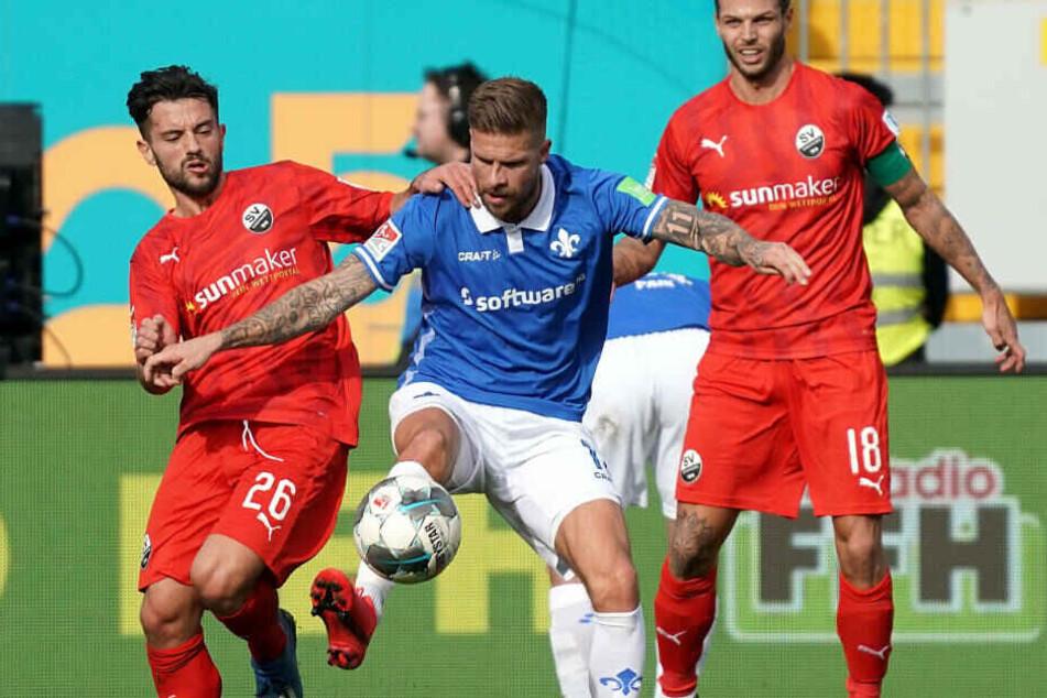 Tobias Kempe (M) sichert gegen Dennis Diekmeier (r) und Besar Halimi (l) aus Sandhausen den Ball.