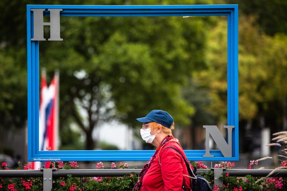 """Eine Frau läuft mit Mund- und Nasenschutz an einem Bilderrahmen mit den Buchstaben """"HN"""" für Heilbronn vorbei."""