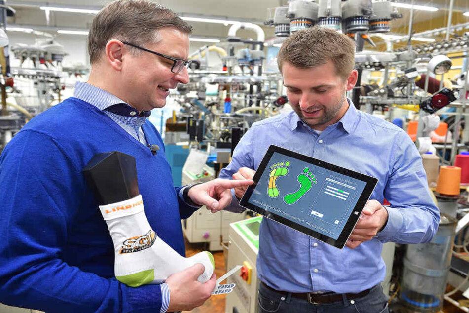 Markus Hill (r.), Wissenschaftlicher Mitarbeiter, und Textilhersteller Thomas  Lindner prüfen die Sensoren der smarten Socke.