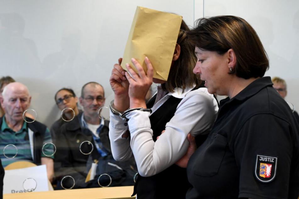 Die Angeklagte verdeckt ihr Gesicht zu Prozessbeginn.