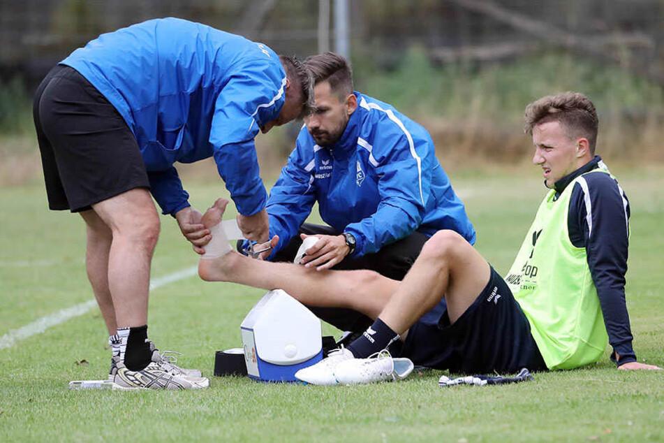 Die ersten Wehwechen gab es auch gleich. Die Physiotherapeuten Olaf Renn und Florian Braband kümmern sich um den am Fuß lädierten Tim Campulka (r.). Er muss die kommenden Tage pausieren.