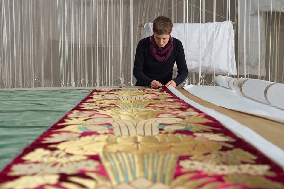 Tapeziererin Julia Modest arbeitet an einem edlen Wandbehang aus Samt.
