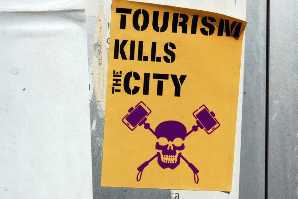 """Manchmal bekommen Touristen den Ärger auch deutlich zu sehen - wier hier in Spanien auf diesem Aufkleber mit der Aufschrift """"Tourismus tötet die Stadt""""."""