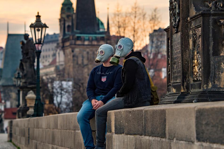 Ein Paar mit Gasmasken sitzt auf der Karlsbrücke in Prag.