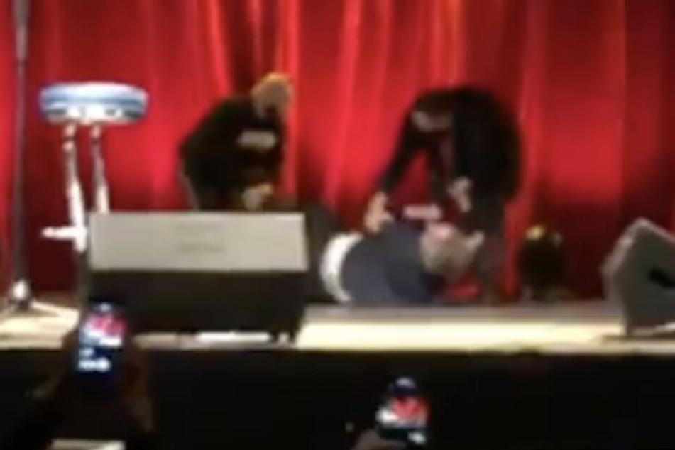 Zwei gut gebaute Männer zerren Schulz über die Bühnenbretter.