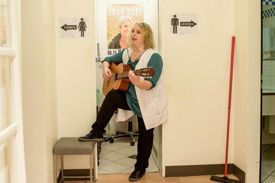 Stefanie Ansul-Weissner steht mit ihrer Gitarre zwischen den Toiletten und singt.