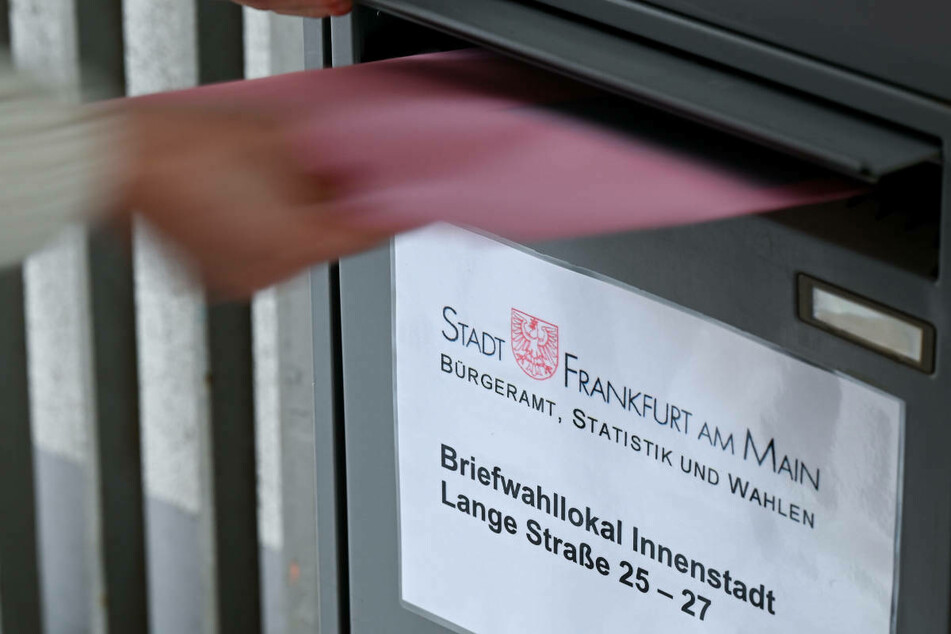 Ein Umschlag mit Briefwahlunterlagen wird am Briefwahllokal Frankfurt Innenstadt in einen Briefkasten geworfen. Frankfurt berichtete zuletzt, die Nachfrage nach Briefwahl sei etwa dreimal so hoch wie 2016.