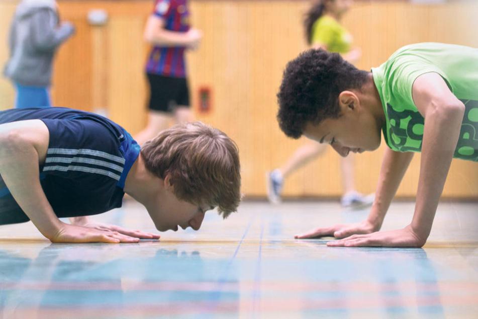 Zwei Jungen machen im Sportunterricht Liegestütze um die Wette. Sie haben dabei gemeinsam viel Spaß am Kräftemessen.