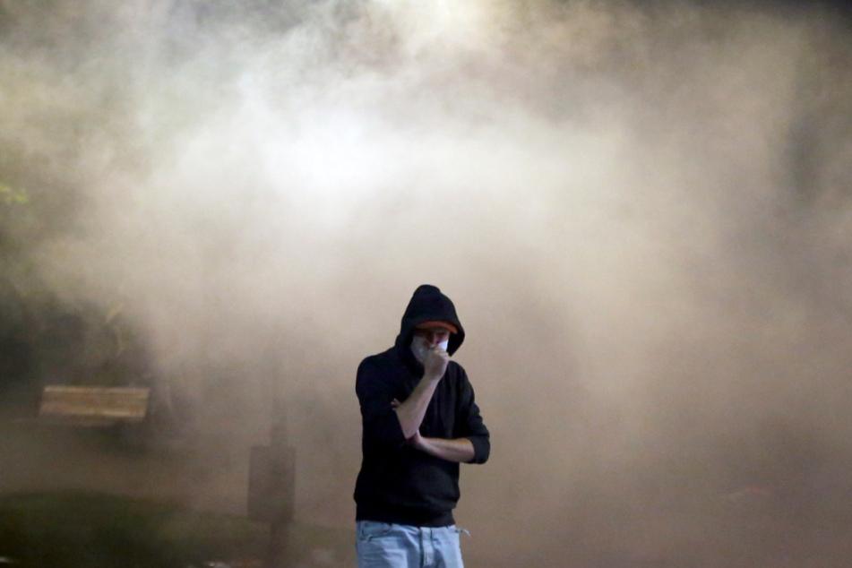 Ein Demonstrant steht während eines Protests gegen die Ankündigung des serbischen Präsidenten protestieren, wieder striktere Corona-Einschränkungen einzuführen, nachdem erneut hohe Todeszahlen gemeldet wurden, in einer Wolke aus Tränengas.