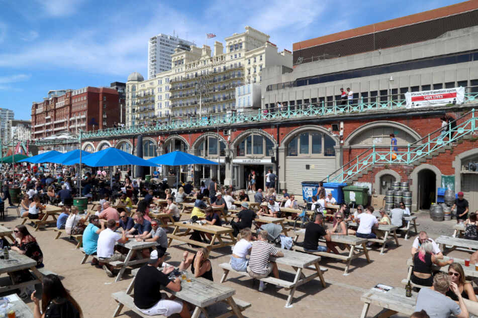 Brighton: Viele Menschen machen es sich auf einer Strandpromenade samt Bar gemütlich.