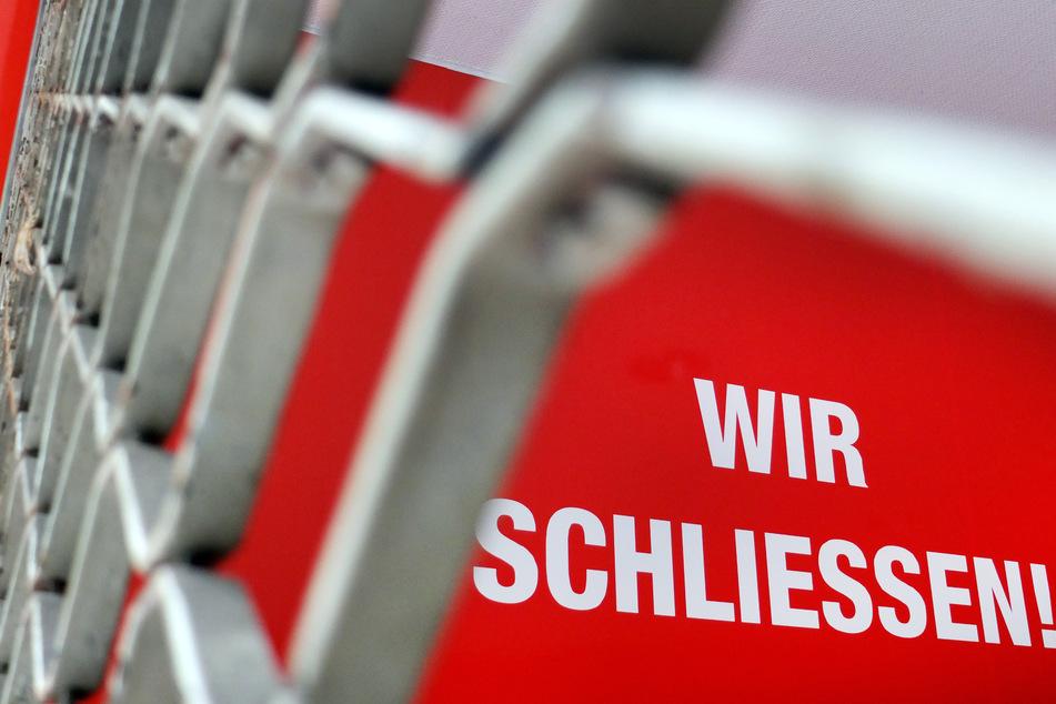 """Der Schriftzug """"Wir Schliessen"""" steht hinter einem Rollgitter an einem geschlossenen Geschäft in Düsseldorf."""