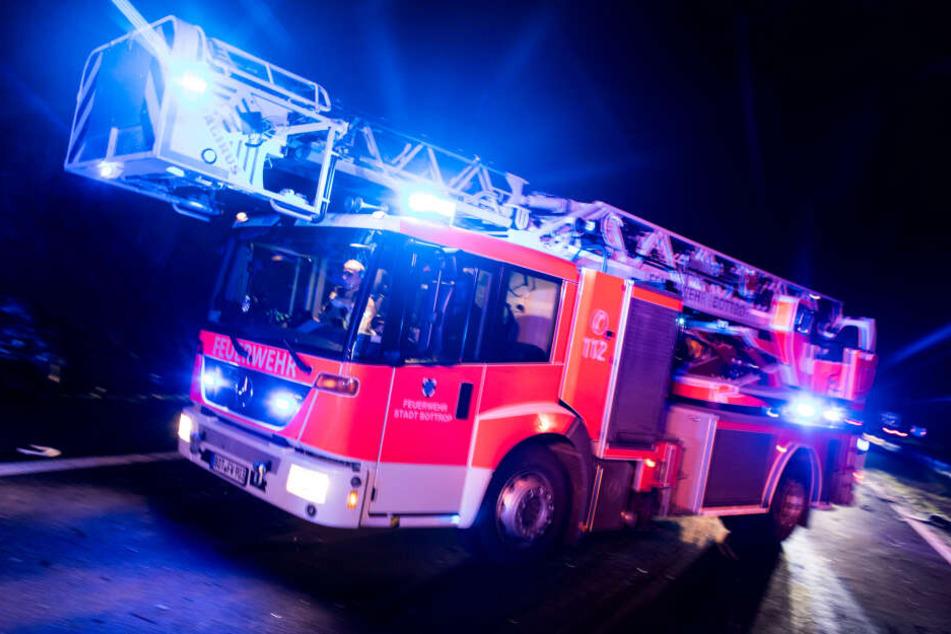 Ein Drehleiterwagen der Feuerwehr fährt mit Blaulicht (Symbolbild).