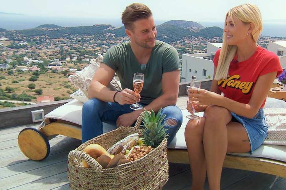 Alex und Bachelorette Gerda sitzen bei einem Glas Sekt zusammen.