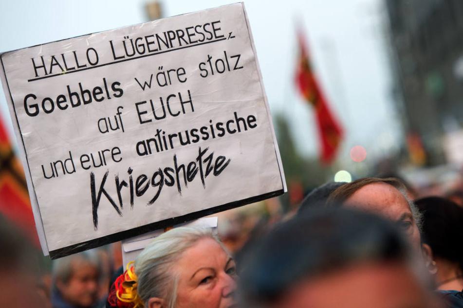 """PEGIDA-Demonstranten halten ein """"Lügenpresse""""-Plakat in die Höhe."""