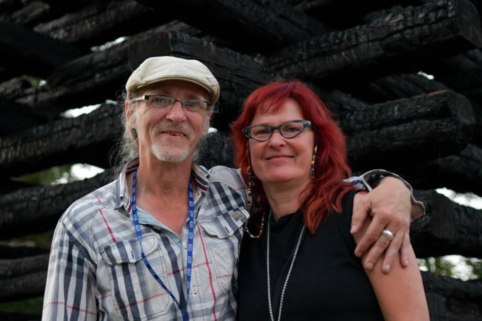 Das Ehepaar Birgit und Horst Lohmeyer steht vor einem Mahnmal bestehend aus den verkohlten Balken ihrer abgebrannten Scheune.