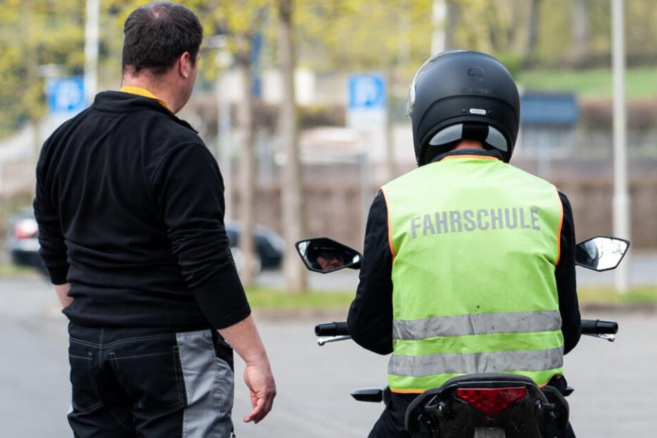 Ein Fahrlehrer erklärt einem Schüler das Motorradfahren. (Symbolbild)