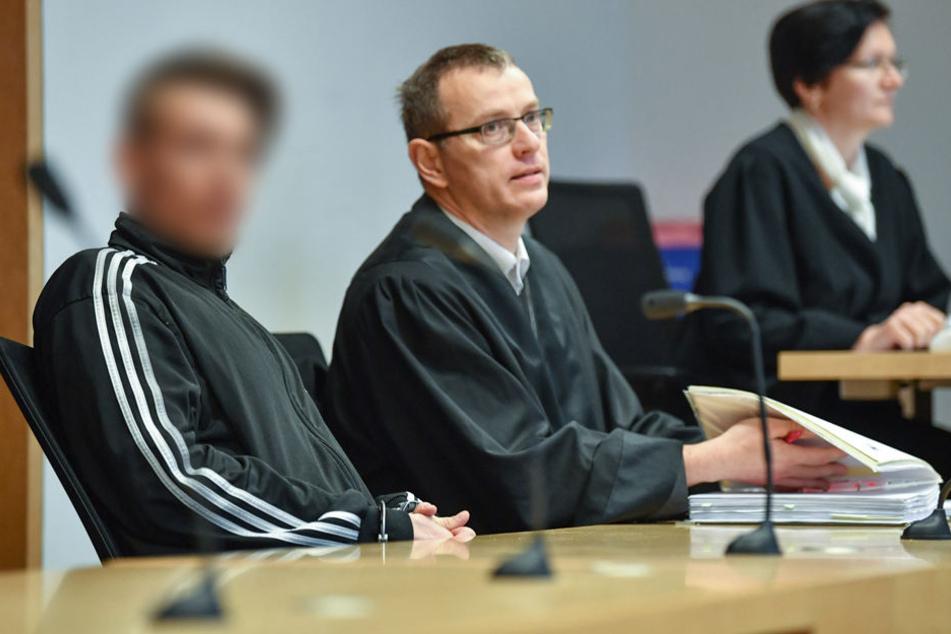 Der Angeklagte (l), im Dreifachmordprozess von Ostbrandenburg, sitzt neben seinem Anwalt Stefan Böhme in einem Verhandlungssaal.