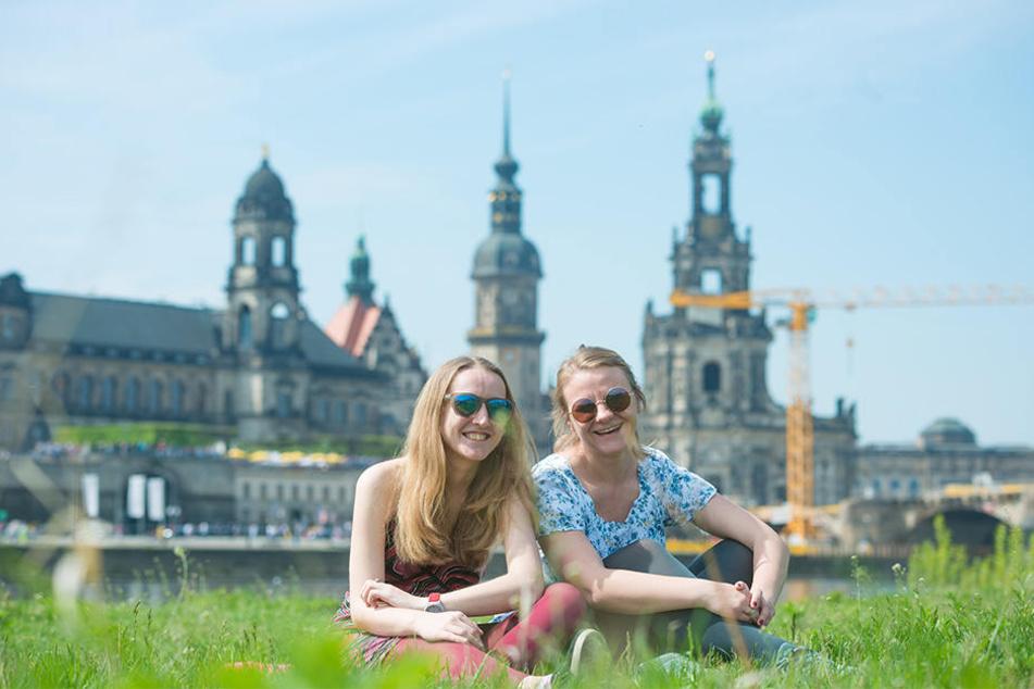 Tanja Dashuk (28, r.) und Hanna Baradzina (30, l.) genießen die Sonnenstrahlen am Elbufer, trotz herumliegender Abfälle.