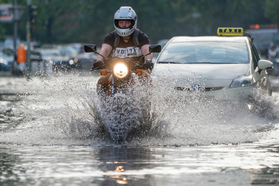 Ein Motorradfahrer fährt vor einem Taxi auf der überfluteten Tiergartenstraße.
