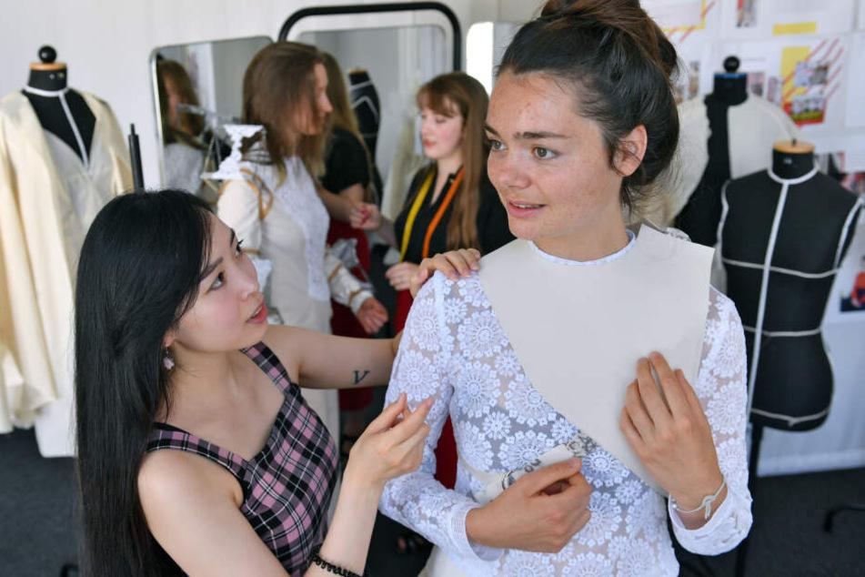 Thuy Tien Phan (l.) und Juliane Mann, Modedesign-Studentinnen der Vitruvius-Hochschule in Leipzig, präparieren ein Outfit mit Stickereien aus Plauener Spitze.